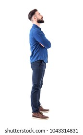 Smart casual bearded business man with crossed arms looking up above. Full body portrait isolated on white background.