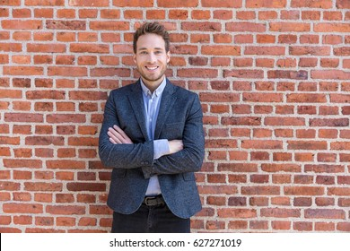 Smart casual businessman in urban city brick wall background lifestyle portrait. Young professional man smiling confident in blazer. Career and entrepreneurship concept.