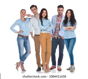 smart casual group of five people standing on white background, with two men in the middle of the women. They are wearing blue shirts and jeans and one man is wearing glasses.