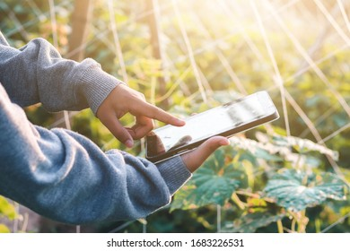 Smart casual man with digital tablet outdoors, close up. Focus on finger. Modern remote work concept.