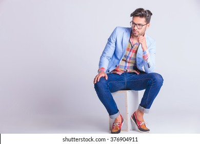 smart casual man seated on box, wearing glasses and jeans, posing while looking away in studio background
