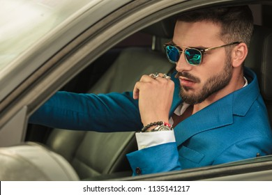 smart casual man with sunglasses and blue suit driving his grey car, portrait picture