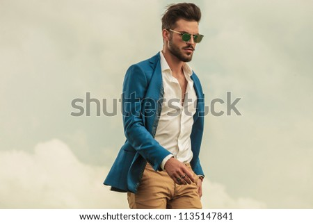 3371dc6095 smart casual man with sunglasses standing on grey clouds background and  looking down to side