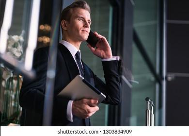 smart caucasian businessman black suit hand hold speaking smartphone walk pass glass entrance door