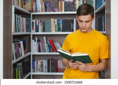 Smart caucasian male student reading book between bookshelves in campus library, empty space