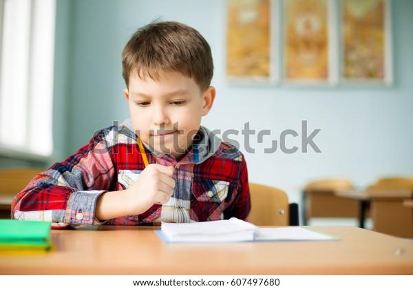 Intelligent, joyeux, heureux, petit, garçon, écolier à la table résout les problèmes et les leçons