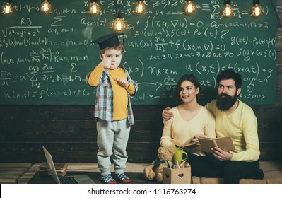 Smart child in graduate cap shows thumb up gesture. Boy presenting his knowledge to mom and dad. Parents listening their son, checking mistakes with book chalkboard on background. Pass exam concept.