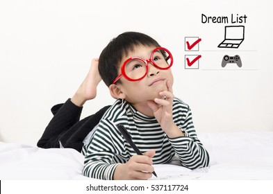 Smart child lying on bed  writing and thinking dream list
