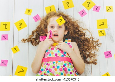 Smart child with question symbol on stickers on his body and around. Stress from studying, homework. Education concept.