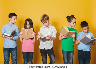 Smart children reading books, standing in row near yellow wall
