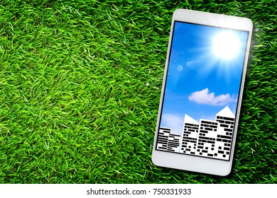 Smart city concept, group of building on green grass background, mobile phone, ecology and nature friendly