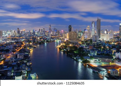 Smart city. Financial district and skyscraper buildings at Chao Phraya River. Bangkok downtown area at night, Thailand.