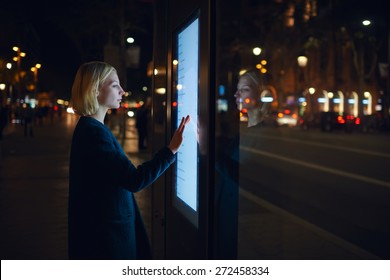Smart city technology concept, young woman using modern urban application of bus stop in Barcelona for find out schedule of transport, female touching big digital screen which reflecting light