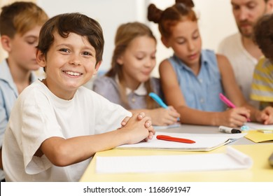 Smart classmates in process of learning new material in classroom. Little pupil sitting together at table and writing in copybook, one of group looking and smiling at camera.