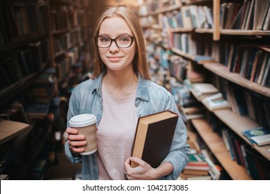 Smart and clever student is standing in the public library. She is holding a cup of coffee and a book at the same time. Girl is looking straight forward with a smile on her face.