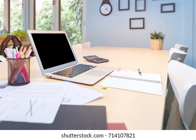 Smart computer and document put on wooden table in Co Working Space, new working office style for startup business owner and freelance.