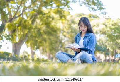 Smart confident Happy young  Asian student in university, Female college student reading book in the green park.