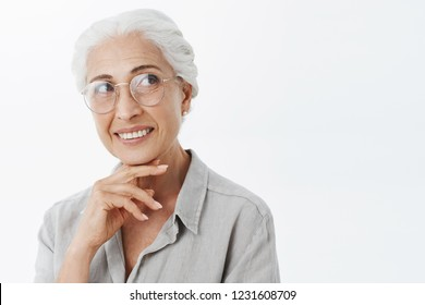 Smart creative and pleased charming granny with white hair in sight glasses smiling curiously holding hand above chin gazing at upper right corner while thinking making decision in mind