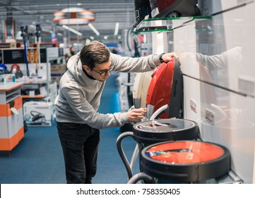 Smart customer buying new vacuum cleaner. Purchasing new home appliances. Modern electronics upgrade. Choice between robot vacuum cleaner and old one. He is examining usuall vacuum cleaner
