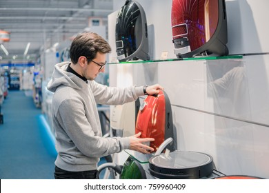 Smart customer buying new vacuum cleaner. Purchasing new home appliances. Choice between robot vacuum cleaner and old one.