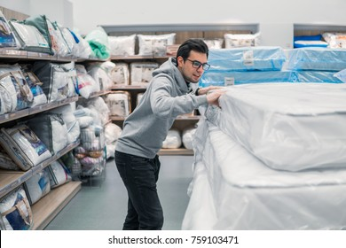 Smart customer man chooses bed linen and bed in the supermarket mall store. He is j examining mattress.