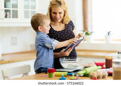 Smart cute child helping mother in kitchen preparing cookies