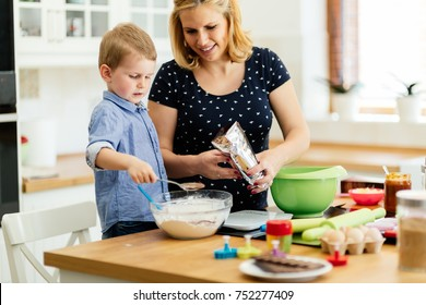 Smart cute child helping mother in kitchen