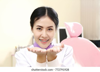 smart cute dentist woman sitting on computer desk with his hand read document, smile and looking at camera, trust responsibility healthcare staff in hospital concept.
