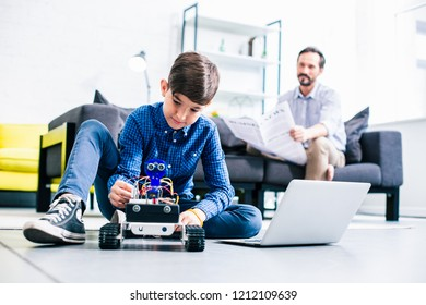 Smart delighted boy testing his robot while preparing for engineering classes