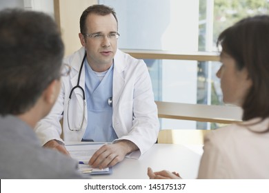 Smart doctor conversing with a cropped couple at hospital desk
