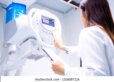 Smart doctor with CT scan machine in lap.