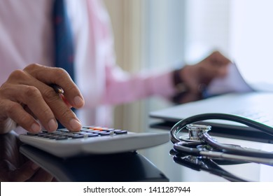Smart doctor hand using calculator for account about medical costs with stethoscope and computer notebook on the desk at modern office,clinic or hospital. Healthcare costs and fees conceptual.