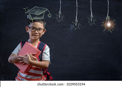 Smart educated school kid student with graduation hat doodle on chalkboard.little boy with paintbrush creative drawing light bulb ideas on wall,