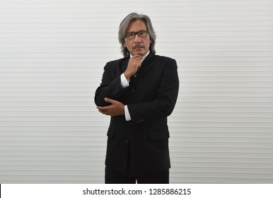 Smart elderly asian businessman in black suit and eyeglasses holding his hand on his chin over white wall background, Business thinking concept