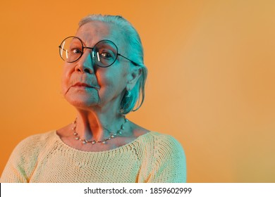 Smart elderly woman in round eyeglasses that gleam reflecting light looks down into camera. Old wise lady with hair combed back isolated over warm orange background
