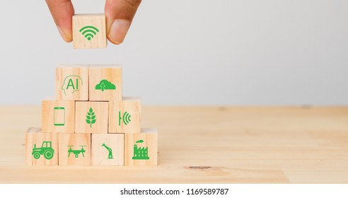 smart farm or agriculture futuristic technology concept, Hand man put the icon connect, icon including wireless wifi, ai or artificial intelligence, cloud, phone, sensor, truck, robot, drone, factory