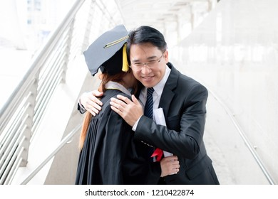 Smart father hugging his daughter at his graduation, parent feeling happiness on Commencement day at the city over background.