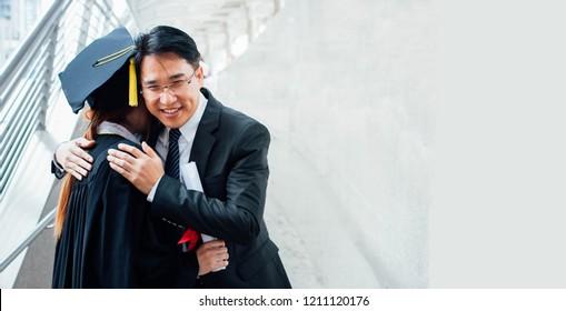 Kluger Vater umarmte seine Tochter bei seinem Abschluss, Eltern fühlen sich glücklich am Tag des Beginns in der Stadt auf dem Hintergrund. Abschluss mit seinem Vater.  Stolzes Umarmungskonzept. Leerzeichen auf der rechten Seite kopieren