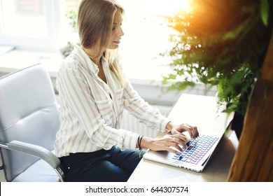 Smart female journalist writing new article on keyboard of laptop computer device connecting to wireless internet connection.Beautiful office manager woman typing text message for sending email
