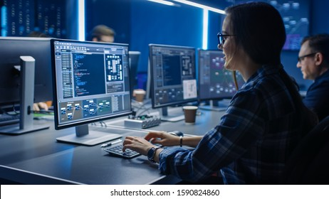 Smart Female IT Programer Working on Desktop Computer in Data Center System Control Room. Team of Young Professionals Doing Code Programming