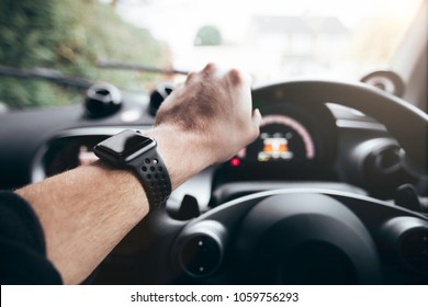 Smart fitness watch on young males wrist whilst driving in the car.