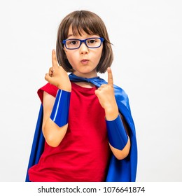 smart fun superhero child with eyeglasses raising her gifted fingers for surprising questions and young critical mindset over white background