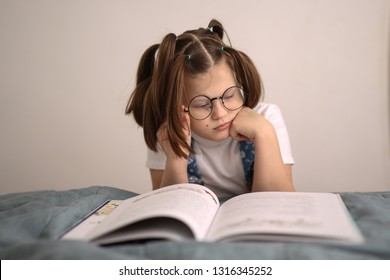 Smart funny fat girl in glasses with funny tails reads a book, concept of childhood and fool's day