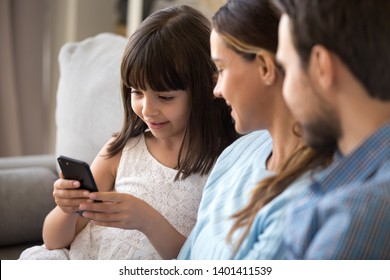 Smart funny preschooler girl sit on couch together with young parents hold smartphone, smiling little child using cellphone playing game or watching cartoon, relax with mom and dad at home