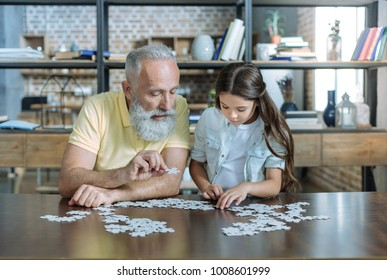 Smart game. Serene elderly man and his granddaughter sitting at a table and looking at puzzle pieces while playing at home together.