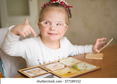 smart girl with Down syndrome collects puzzles