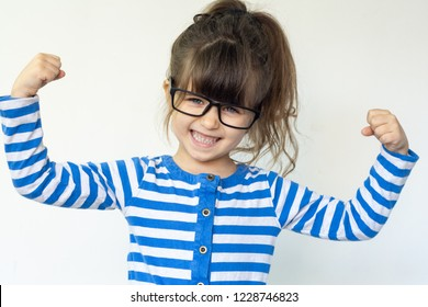 Smart girl flexing his muscles. Isolated over white. Funny strong child with eye glasses