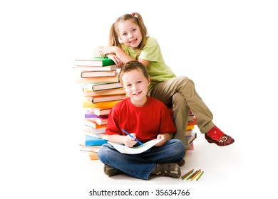 Smart girl sitting on book pile and cute schoolboy looking at camera