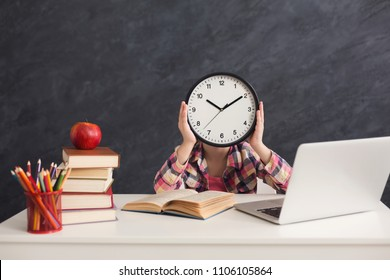 Smart girl sitting with stack of books and laptop, holding big clock, covering face. Education, development, time management, deadline, time to study, school concept