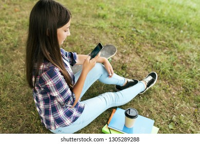 Smart girl teenager 13-16 years old, sitting in summer in city park. Happy smiling, writing message in social networks online. Nearby are notebooks with documents, skateboard and cup coffee or tea.